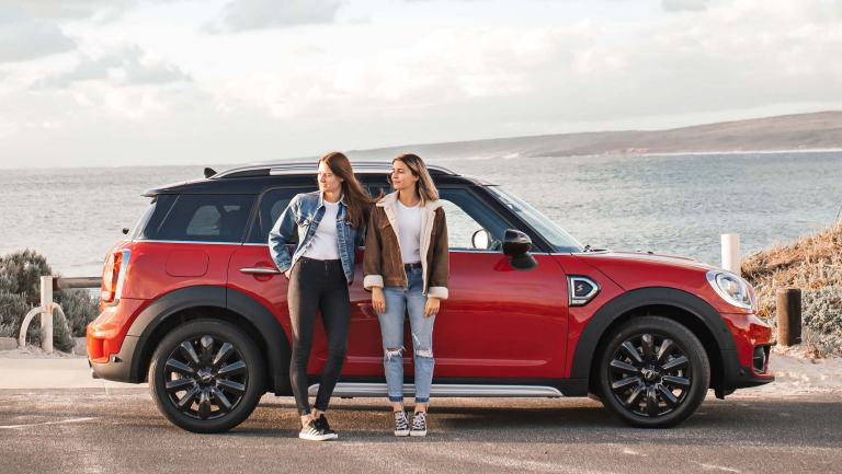 A red MINI with two woman standing in front